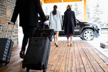 Bellhop with suitcases following businesswomen leaving hotel Fototapete