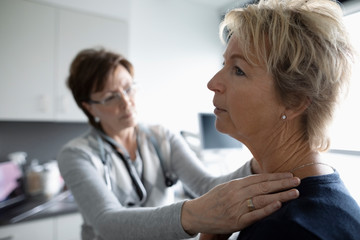 Female doctor examining patient s neck in clinic examination room