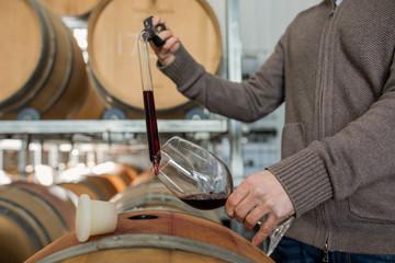 Winemaker checking wine in barrels at vineyard