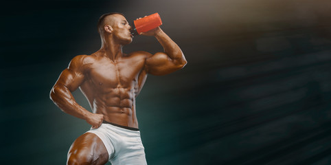 Nutritional Supplement. Muscular Men Drinks Protein, Energy Drink After Workout. Copy Space