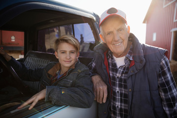 Portrait confident grandfather and grandson at truck on farm