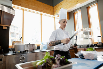 Female chef with tattoos sharpening knife in restaurant kitchen