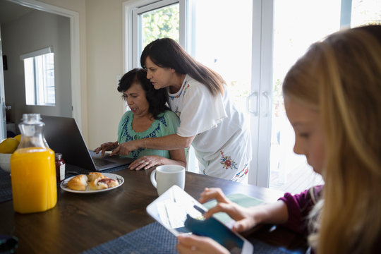 Latinx daughter teaching senior mother how to use laptop at dining table