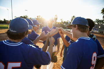 Baseball players joining fists in huddle on sunny field