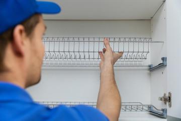 furniture service worker installing kitchen cabinet dish rack