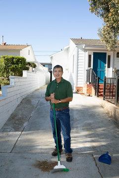 Portrait confident Latinx senior man sweeping driveway