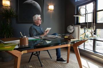 Thoughtful senior man using digital tablet in modern home office Fototapete