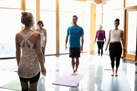 Female instructor leading yoga class in studio