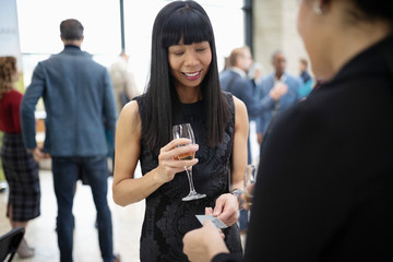 Smiling businesswomen drinking champagne, networking and exchanging business cards at conference