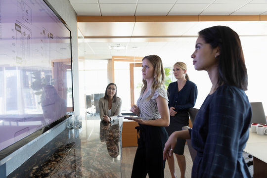 Female architects reviewing digital blueprint on television screen in conference room meeting