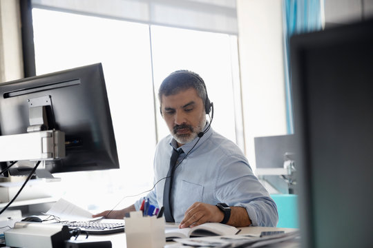 Businessman with headset working at computer in office