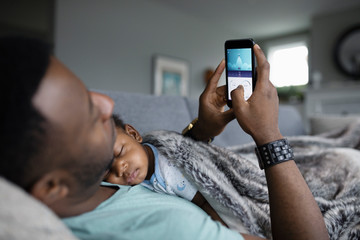 Father using smart phone with baby son sleeping on chest