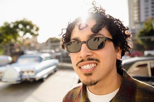 Portrait smiling, confident Latinx man in sunny parking lot