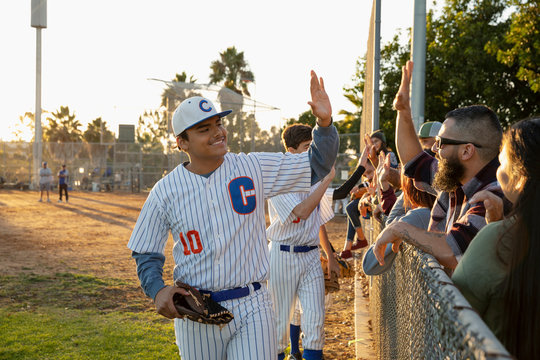 Latinx baseball player high-fiving fans at fence