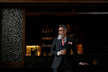Fashionable hipster businessman with beard drinking cocktail in bar