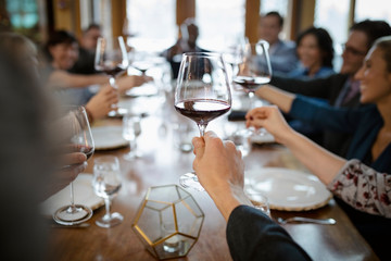 Business people toasting red wine glasses at restaurant table