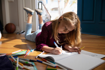 Girl coloring on floor