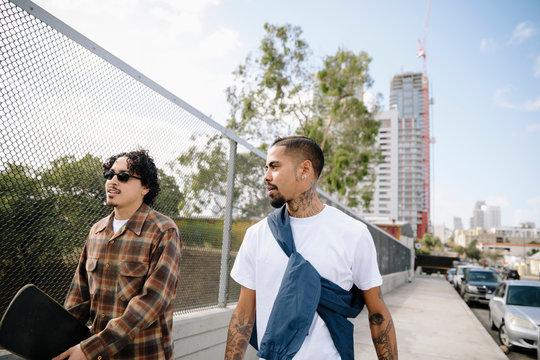 Latinx young men with skateboard walking on urban sidewalk