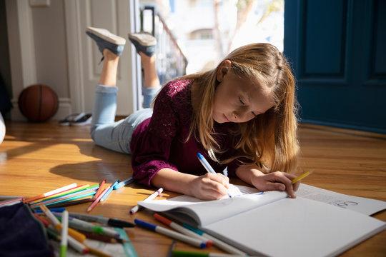 Girl coloring on floor
