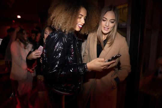 Women friends using smart phone in nightclub queue