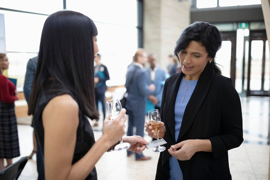 Businesswomen networking, drinking champagne and exchanging business cards at conference
