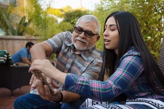 Latinx grandfather and granddaughter using smart phone on patio