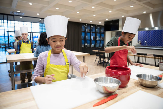Children flouring surface in cooking class