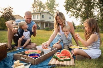 Young family enjoying picnic in rural yard