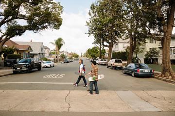 Latinx young men with skateboards crossing neighborhood street Fototapete