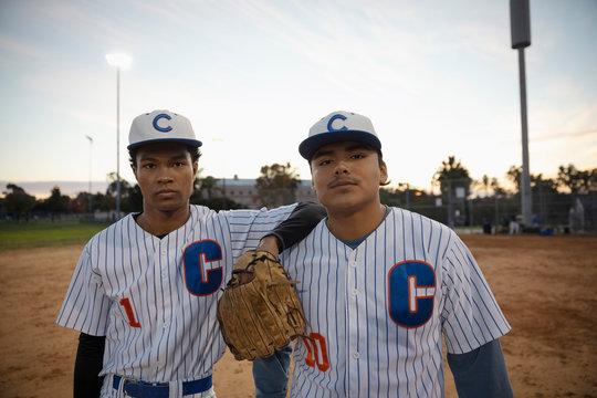 Portrait confident Latinx baseball players on field at night