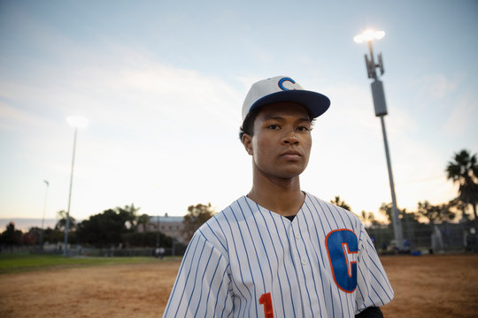 Portrait confident, determined Latinx baseball player on field at dusk