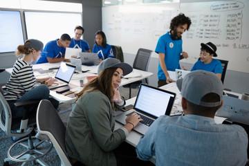 Hackers using laptops, talking during hackathon