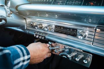 Close up man adjusting dial in low rider vintage car