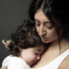 Serene Latina woman holding toddler daughter
