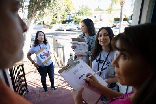 Latinx female volunteers canvassing voters door-to-door