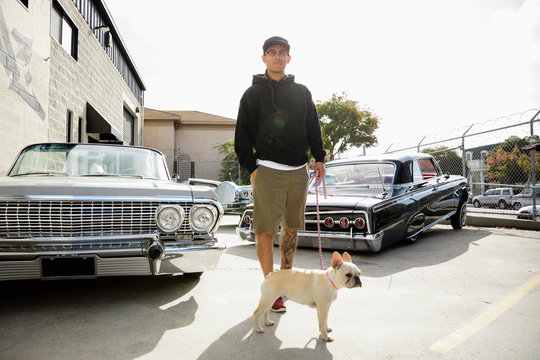 Portrait Latinx young man with French bulldog in parking lot with low rider cars