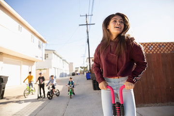 Latinx tween girl playing with pogo stick in alley