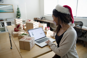 Young woman in Santa hat shopping online at laptop surrounded by Christmas gifts