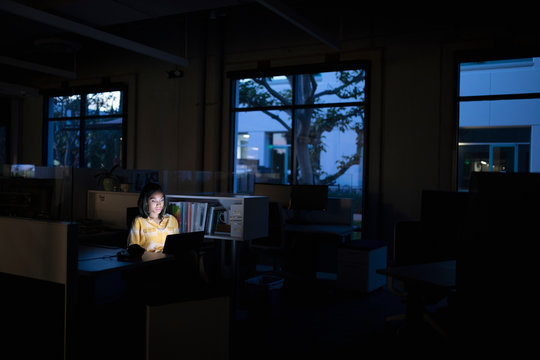 Businesswoman working late at laptop in dark office