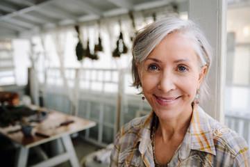 Portrait smiling, confident senior woman in workshop