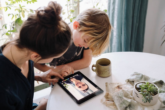 Mother and son using digital tablet at table