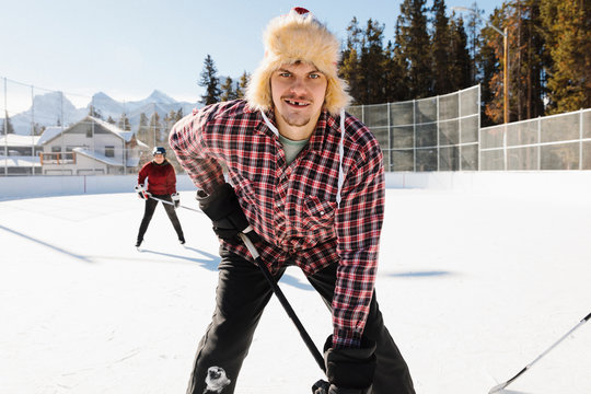 Portrait confident man playing outdoor ice hockey