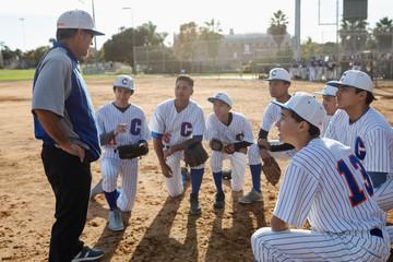 Coach and baseball team huddling on field