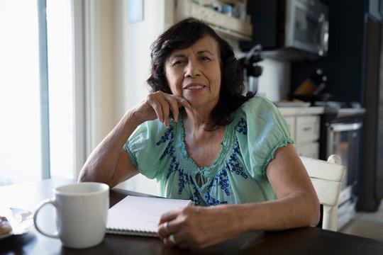 Portrait confident Latinx senior woman making a list at kitchen table