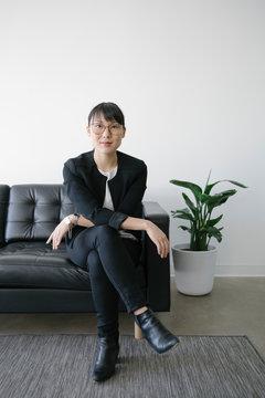 Portrait confident businesswoman on leather sofa