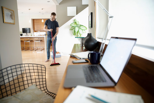 Man taking a break from working at home,s weeping floor