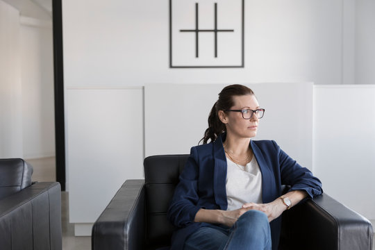 Thoughtful businesswoman sitting in leather armchair in office lobby