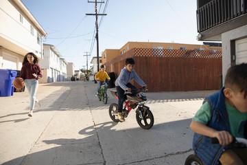 Latinx children playing, riding bikes in alley
