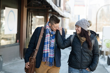 Affectionate lesbian couple walking, holding hands on urban sidewalk