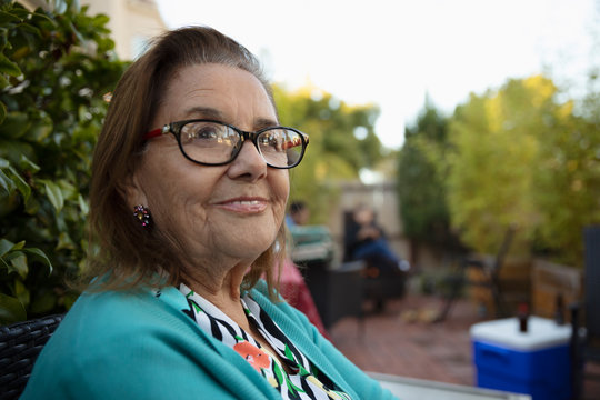 Portrait confident Latinx senior woman on patio